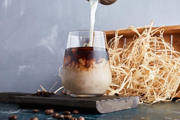 Eine tasse kaffee und mehr milch hinzufügen.
