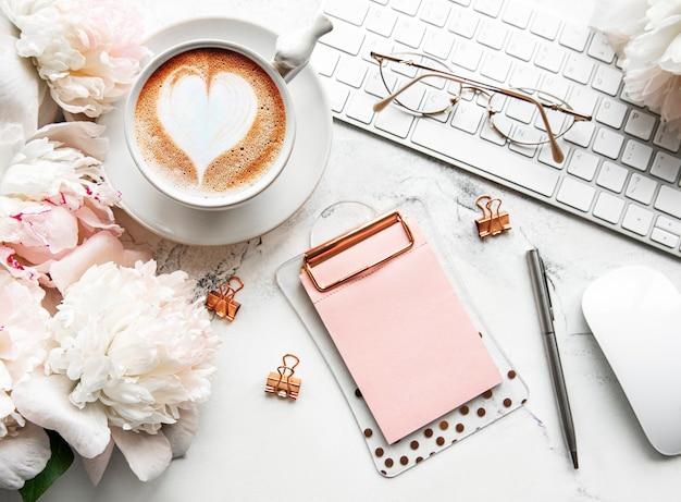 Eine tasse kaffee und pfingstrosenblumen auf dem schreibtisch