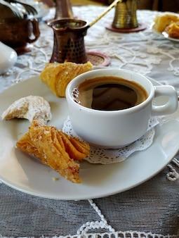 Eine tasse kaffee und süßigkeiten auf einer untertasse, kaffee in einem türken stehen auf einer weiß bestickten tischdecke.