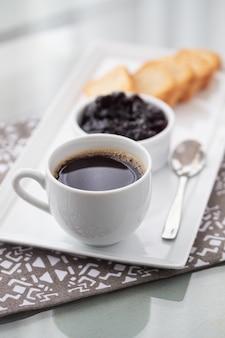 Eine tasse kaffee und toast mit preiselbeermarmelade auf weiß