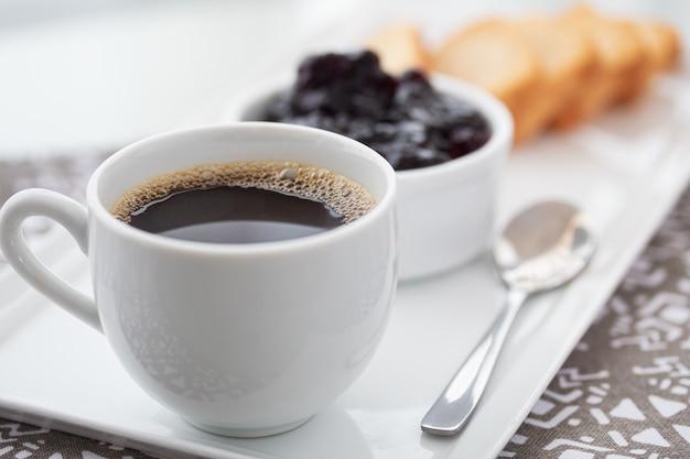 Eine tasse kaffee und toast mit preiselbeermarmelade auf weiß.