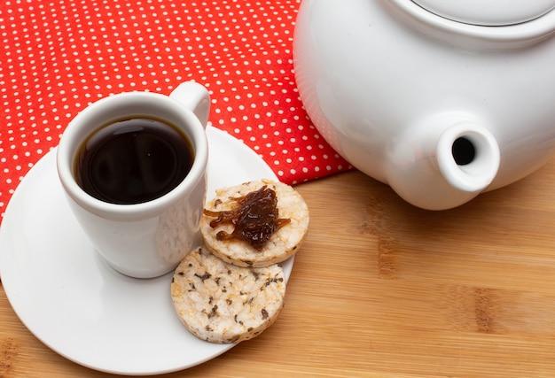 Eine tasse kaffee unter dem strohtisch, umgeben von einer kaffeekanne