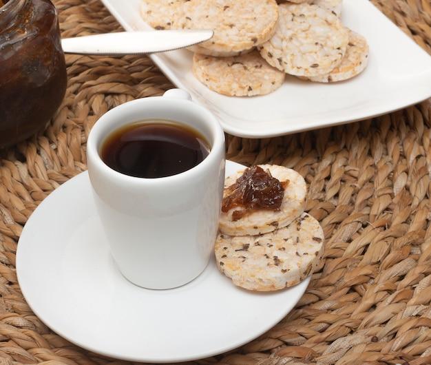 Eine tasse kaffee unter dem strohtisch, umgeben von einer schüssel voller reiskekse und einem geleetopf