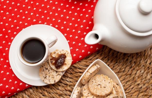 Eine tasse kaffee unter dem strohtisch, umgeben von einer schüssel voller reiskekse und einer kaffeekanne