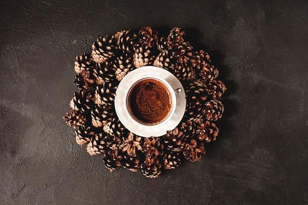 Eine tasse kaffee, viele zapfen herum. draufsicht mit platz für text