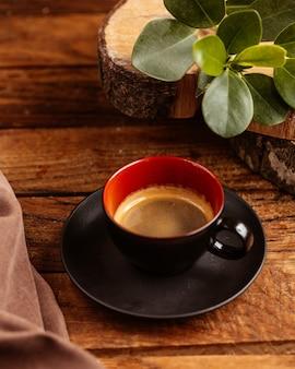 Eine tasse kaffee von oben, die in der schwarzen tasse auf dem braunen holztisch halb leer ist, trinkt kaffeeflüssigkeit