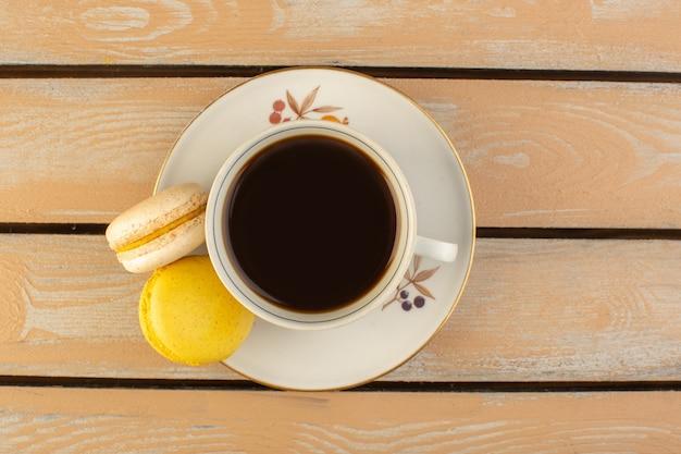Eine tasse kaffee von oben heiß und stark mit französischen macarons auf dem cremefarbenen rustikalen schreibtisch trinken kaffee foto stark