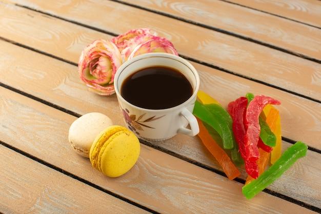Eine tasse kaffee von oben heiß und stark mit französischen macarons blumen und marmelade auf dem cremefarbenen rustikalen schreibtisch trinken kaffee foto süßer keks