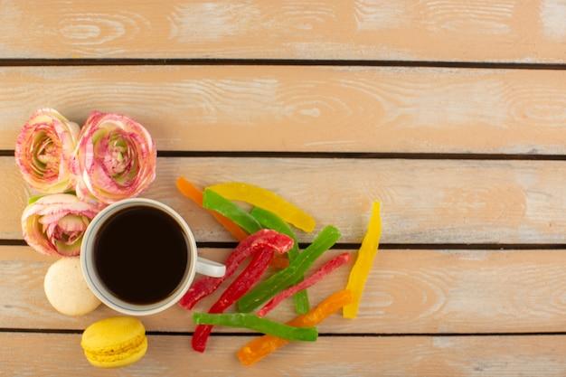 Eine tasse kaffee von oben heiß und stark mit französischen macarons und marmelade auf dem cremefarbenen rustikalen schreibtisch trinken kaffee foto süßer kekszucker