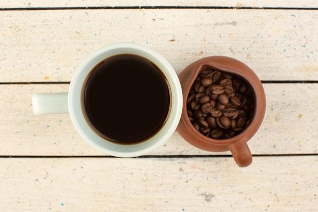 Eine tasse kaffee von oben in der weißen tasse mit frischen braunen kaffeesamen