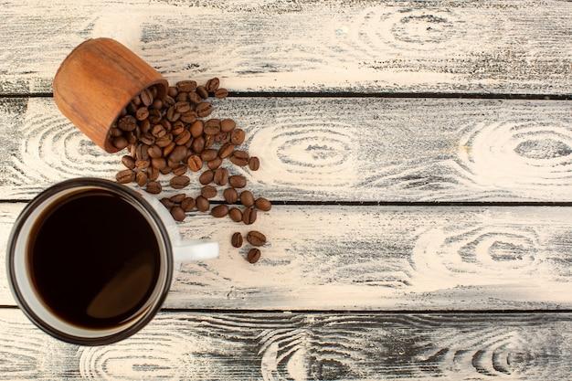 Eine tasse kaffee von oben mit braunen kaffeesamen auf dem grauen rustikalen schreibtisch trinken kaffeefarbe