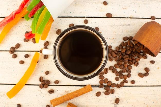 Eine tasse kaffee von oben mit frischem braunem kaffeesamen, zimt und bunter marmelade