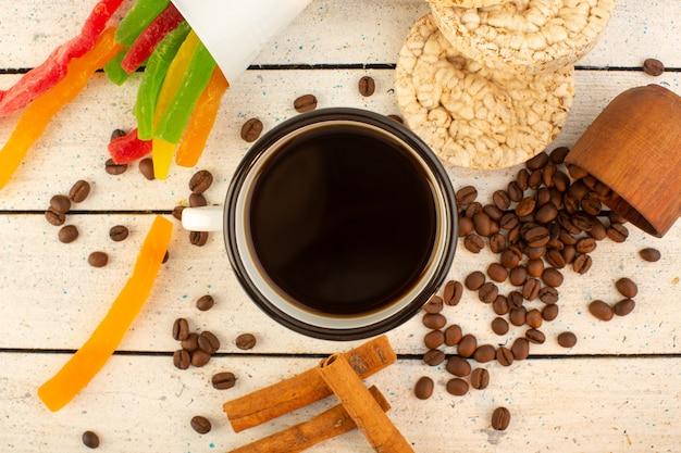 Eine tasse kaffee von oben mit frischen braunen kaffeesamen, zimtcrackern und bunter marmelade