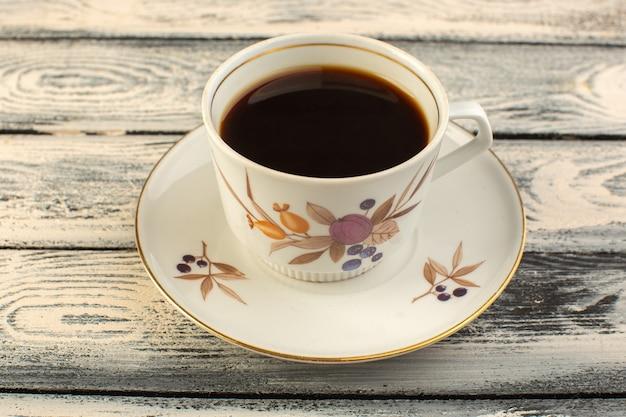 Eine tasse kaffee von vorne, heiß und stark auf dem grauen rustikalen schreibtischkaffee-heißgetränk
