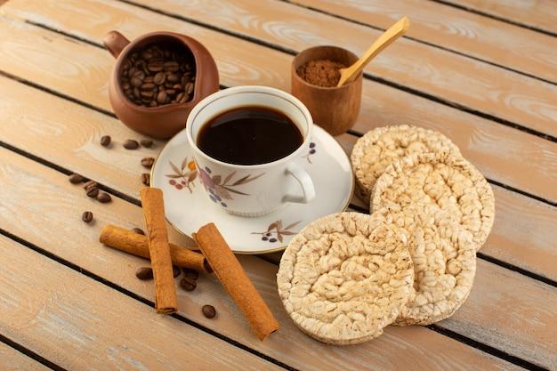 Eine tasse kaffee von vorne, heiß und stark mit frischen braunen kaffeesamen und crackern auf dem cremefarbenen rustikalen schreibtischkaffee-samengetränk-fotokorn