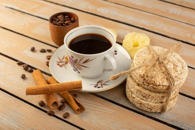 Eine tasse kaffee von vorne, heiß und stark mit frischen braunen kaffeesamen, zimt und crackern auf dem cremefarbenen rustikalen schreibtischkaffee-samengetränk-fotokorn