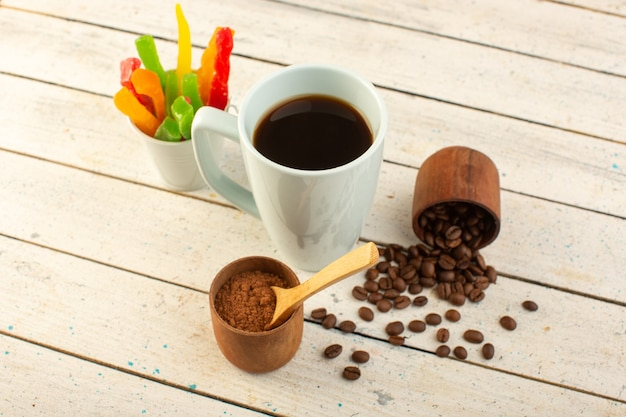 Eine tasse kaffee von vorne in weißer tasse mit frischen braunen kaffeesamen und marmelade auf der hellen oberfläche trinken kaffeekoffein