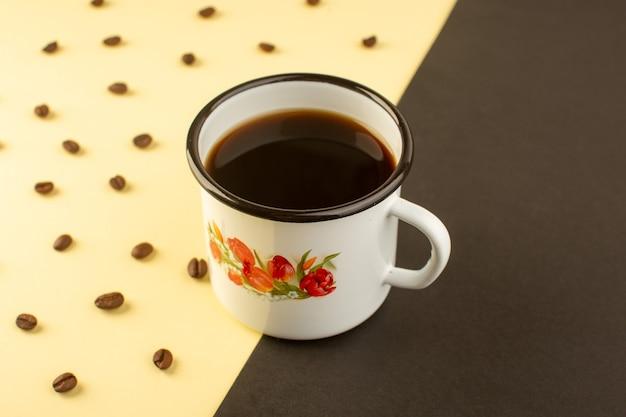 Eine tasse kaffee von vorne mit braunen kaffeesamen auf der gelb-dunklen oberfläche trinkt kaffeekorn