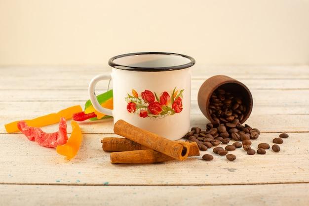 Eine tasse kaffee von vorne mit frischem braunem kaffeesamen, zimt und bunter marmelade auf dem hellen kaffeekoffein