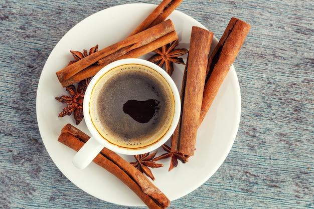 Eine tasse kaffee, zimtstangen und anissterne