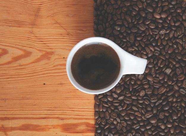 Eine tasse kaffee zwischen einer holzoberfläche und gerösteten kaffeebohnen.
