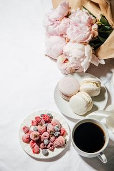 Eine tasse kaffeebeeren makronen und pfingstrosenblüten auf dem bett