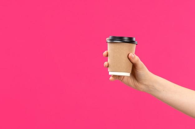 Eine tasse kaffeehand der vorderansicht, die rosa hintergrundfarbgetränk der männlichen männlichen hand hält