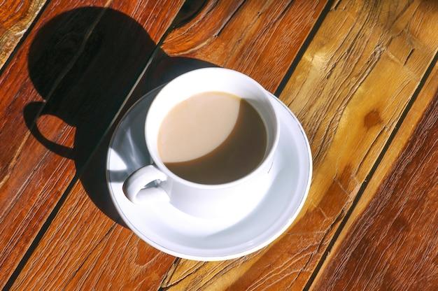 Eine tasse kaffeemilch auf holztisch