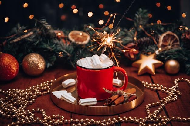 Eine tasse kakao mit marshmallows zu neujahr und eine brennende wunderkerze.