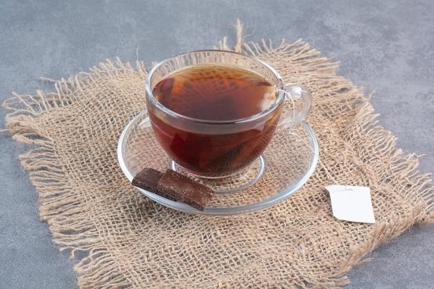Eine tasse köstlichen aroma-tee auf sackleinen.