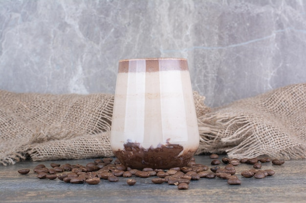 Eine tasse köstlichen kaffee mit kaffeebohnen auf holzbrett. foto in hoher qualität