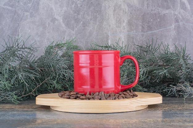 Eine tasse köstlichen kaffee mit kaffeebohnen auf holzbrett
