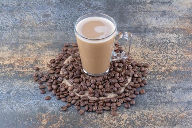 Eine tasse köstlichen kaffee mit kaffeebohnen auf marmor