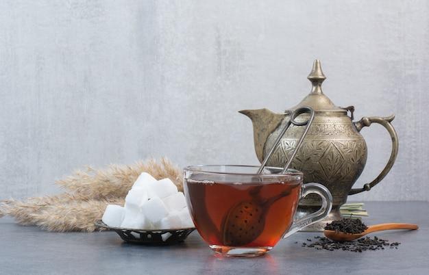 Eine tasse köstlichen tee mit altem wasserkocher und zucker.