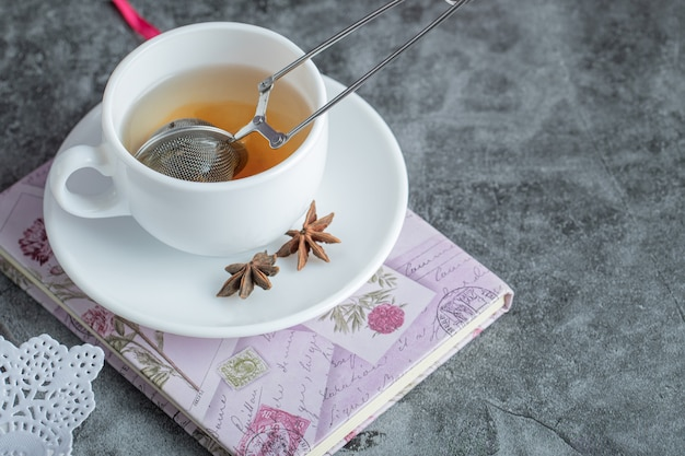 Eine tasse köstlichen tee mit sternanis auf weißem teller.