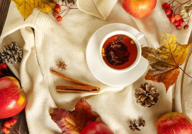 Eine tasse kräuter-hibiskus-tee auf dem hintergrund eines gestrickten weißen pullovers mit äpfeln und blättern