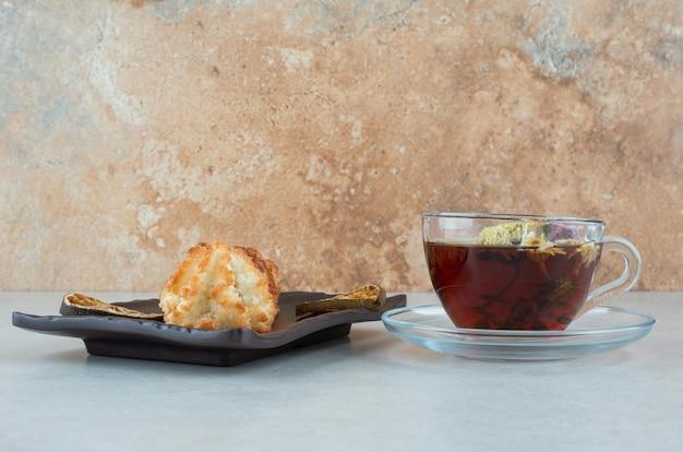 Eine tasse kräutertee mit keksen und getrockneten orangen auf schwarzem teller.