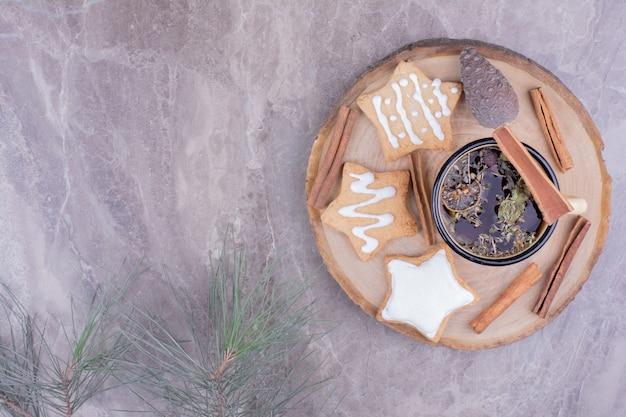 Eine tasse kräutertee mit lebkuchen auf einem holzbrett