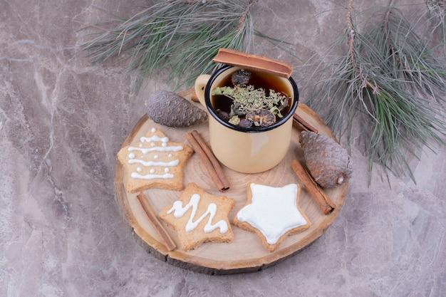 Eine tasse kräutertee mit sternförmigen lebkuchen auf einem holzbrett