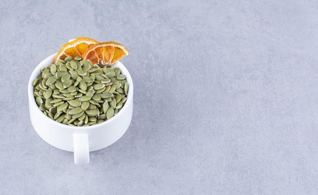 Eine tasse leckere kürbiskerne mit getrockneter zitrone auf der marmoroberfläche