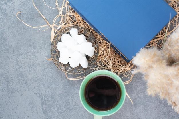 Eine tasse leckeren tee mit buch und zucker auf heu