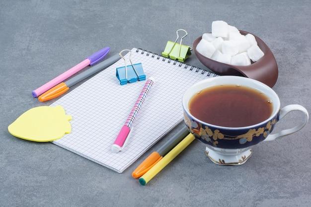 Eine tasse leckeren tee mit stiften und blatt papier