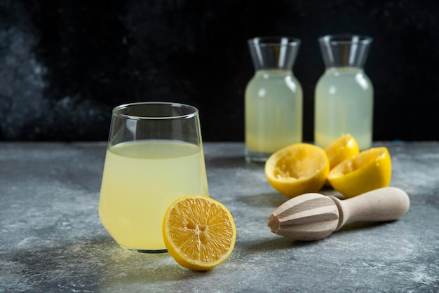 Eine tasse limonade mit zitronenscheiben und holzreibahle.