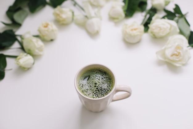 Eine tasse matcha-tee und rosen auf weißem hintergrund flatlay-draufsicht