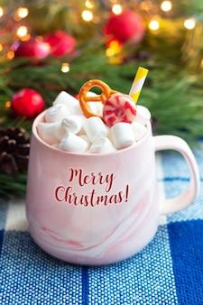 Eine tasse mit dem text frohe weihnachten mit marshmallow auf einem hintergrund eines zweiges eines weihnachtsbaums