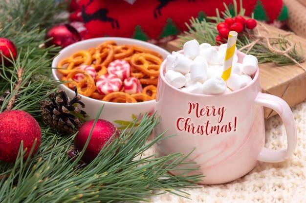 Eine tasse mit dem text frohe weihnachten mit marshmallow in der nähe eines zweiges eines weihnachtsbaums brezeln