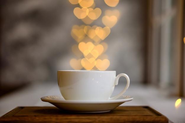 Eine tasse mit einem heißen, belebenden morgengetränk mit lichtern in form von herzen