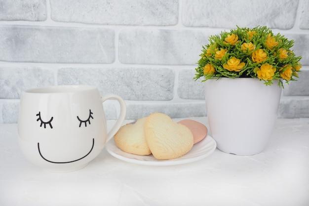 Eine tasse mit einem lustigen gesicht, ein teller mit keksen und herzen und eine künstliche blume in einem blumentopf auf dem tisch