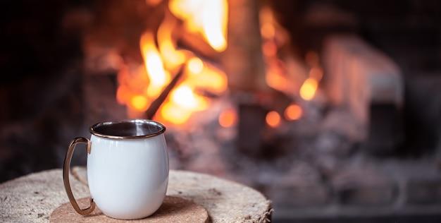 Eine tasse mit einem wärmenden getränk auf einem unscharfen hintergrund eines brennenden feuers. outdoor-erholungskonzept.