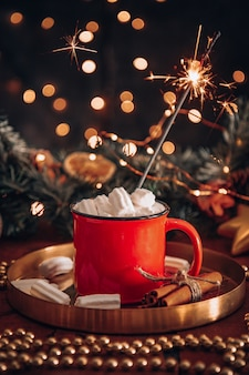 Eine tasse mit kakao mit marshmallows in einer neujahrsumgebung und einer brennenden wunderkerze,